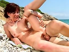 Spanish MILF fucks young stud on the beach